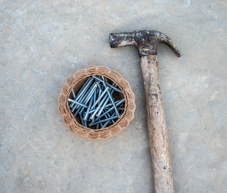 concrete tack with a basket and hammer on the floor Stock Photo