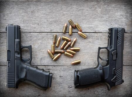 two handgun and bullet on old wood background Banque d'images