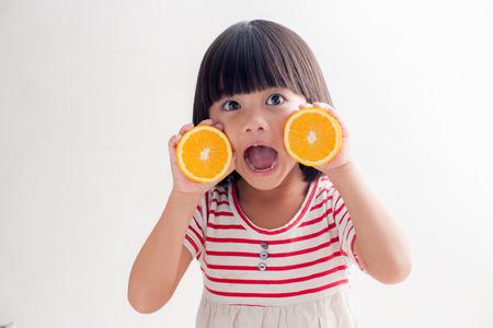 naranja: Niña que juega con frutas de color naranja