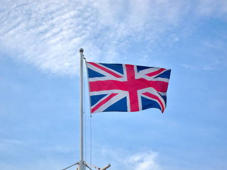 Flag of the United Kingdom on a blue sky background. Stock Photo