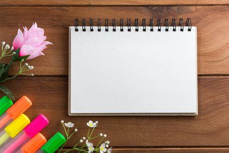 wooden floor: Notebook with a pen on a white wooden floor highlights. Stock Photo