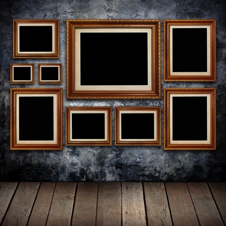 gallery interior: Grungy wall with gold frames and old wood background.