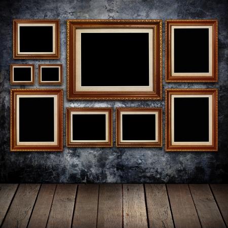 galeria fotografica: Sucia pared con marcos dorados y fondo de madera vieja. Foto de archivo