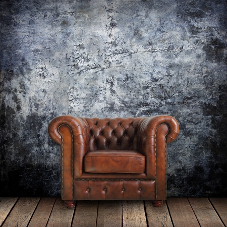 grime: Grungy wall with Classic Brown leather armchair and old wood background.
