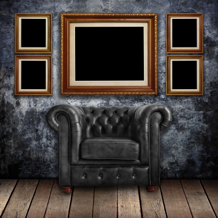 gallery interior: Grungy wall with Classic Brown leather armchair and gold frames background  Stock Photo