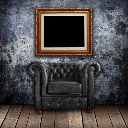 Grungy wall with Classic Brown leather armchair and gold frames background Stock Photo - 12801665