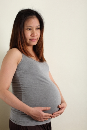 Pregnant asian woman caressing her belly  Warm tone color  photo