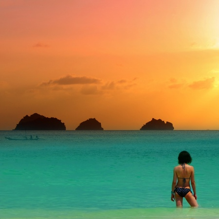 Beauty girl in bikini at the sea is standing knee-deep in water on sunset background  photo