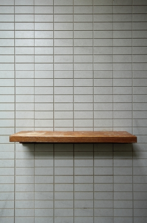Empty wooden shelf on the tile wall  photo