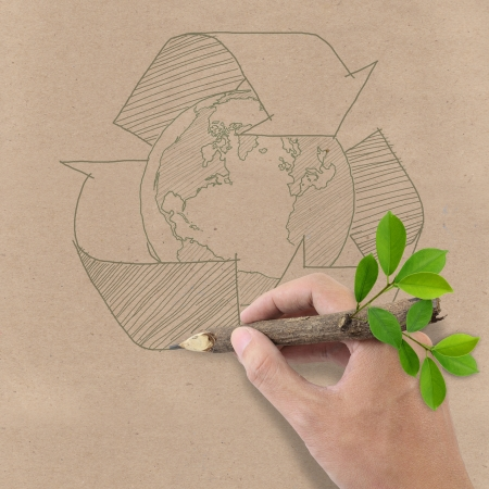 recycling plant: Male hand drawing recycle and earth symbol on Brown Recycled Paper  Stock Photo