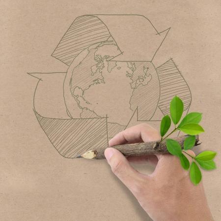 reciclable: Masculino mano que dibuja reciclaje y la tierra símbolo en papel reciclado Brown Foto de archivo