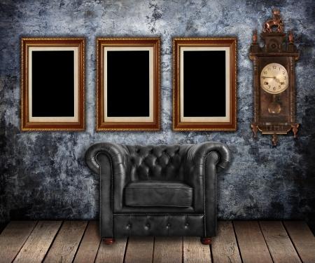 Poltrona classica in pelle e vecchio orologio con cornici dorate sulla parete Grungy