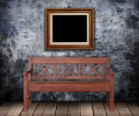 furniture detail: Wooden bench with Gold frames on Grungy wall