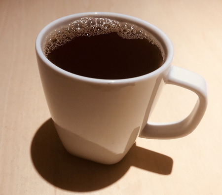 Coffee cup on brown background.