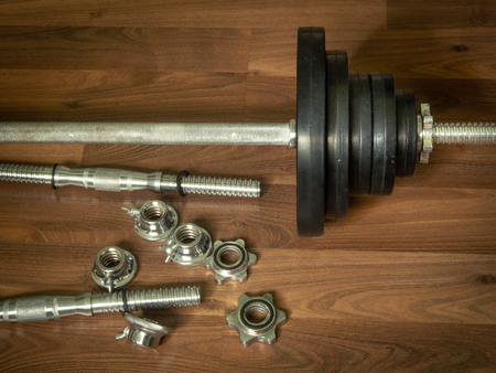 Dumbbell barbell on brown wood background.