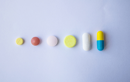 different Tablets pills capsule heap mix therapy drugs on white background