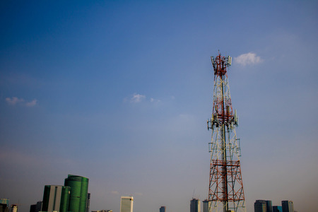 Communication Tower in city on Blue Sky background Stock Photo
