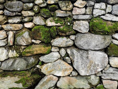 Stone wall with green moss texture Background with copy space. 写真素材