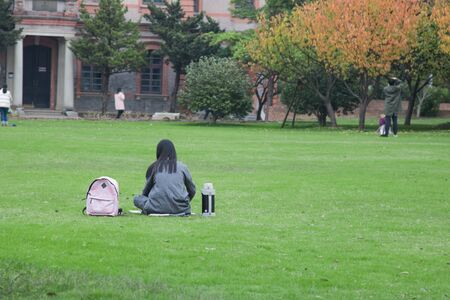 Young woman relaxing outdoors   on the lawn in public park