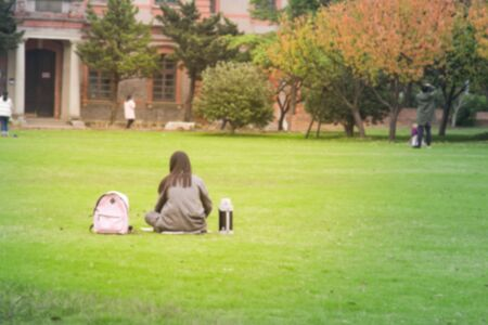 Abstract blur Young woman relaxing outdoors   on the lawn in public park,abstract blur background 版權商用圖片