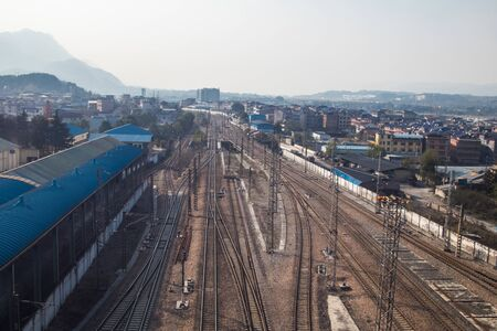 Perspective view on many railway track lines, Old platform and freight train nearby. Railroad background.