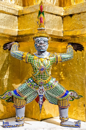 Thai giant stand in front of gold pagoda in Wat Phra Keaw,Bangkok ,Thailand photo