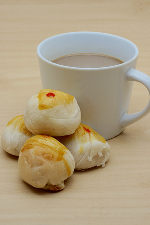 cup four: Cup of coffee and four chinese pastry on wooden background.
