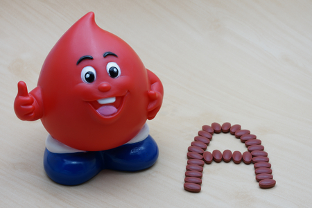 ferrous: Ferrous Fumarate 200 mg with Vitamins for blood donor type A after donating blood on wood background.