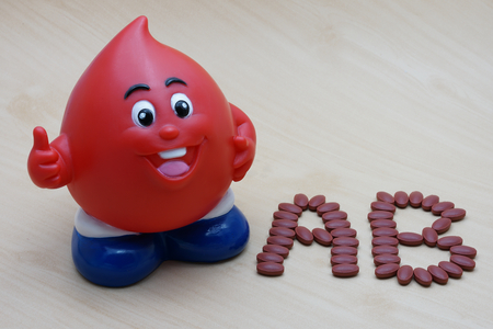 ferrous: Ferrous Fumarate 200 mg with Vitamins for blood donor type AB after donating blood on wood background.