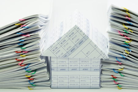 dual: House between dual pile overload document with colorful paperclip on white background. Stock Photo
