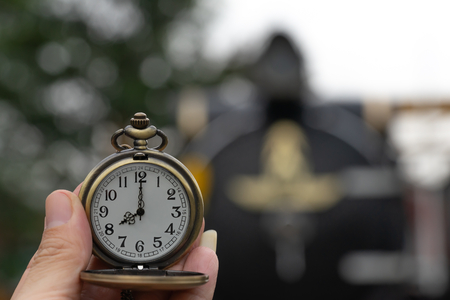 Clock with lid shows at 8 oclock in hand on steam Locomotives blurred background. Banco de Imagens