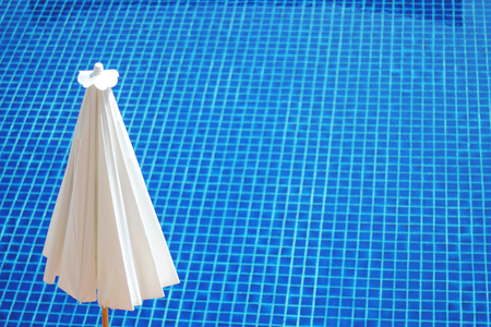 White umbrella by the blue swimming pool Stock Photo
