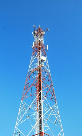 Red and white tower of communications with their telecommunications antennas