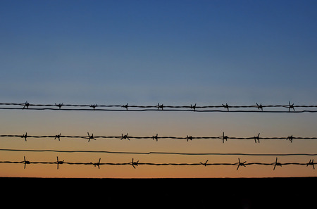 invade: Rusty barbed wire with sunset background Stock Photo