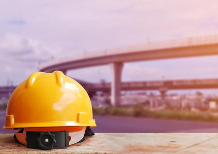 ingeniero civil: Casco de seguridad con el fondo de sitio de construcci�n de carreteras Foto de archivo
