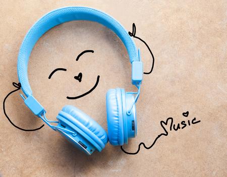 ear phones: Blue headphones with cartoon listening music on wooden background