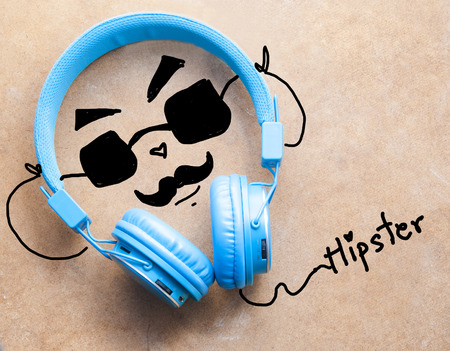 listening to music: Blue headphones with hipster man listening music on wooden background Stock Photo