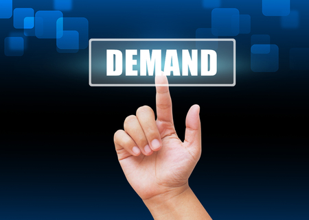 in demand: Hand pressing Demand button with technology background