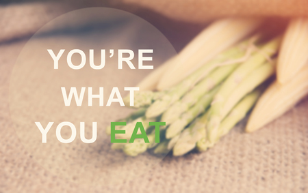 what to eat: The text Youre what you eat on Fresh asparagus prepare on gunny-bag background