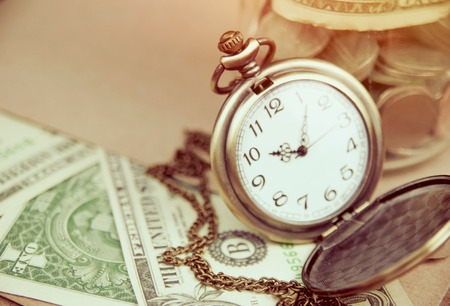 dept: Money saving concept with vintage clock for the past. Stock Photo