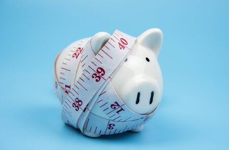Piggy bank with measuring tape isolated on blue pastel background,healthy or over weight concept Stock Photo