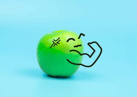 Strong cartoon character on green apple isolated on blue pastel background, healthy   or diet concept Stock Photo