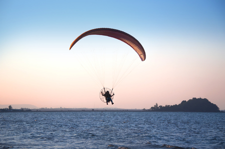 Parachute flying on sea beach with sunset background