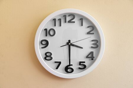 Wall clock at 3.30 am/pm on cream color background.