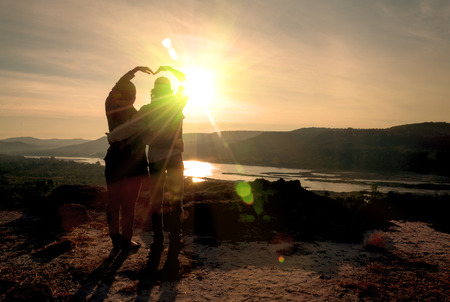 baiser amoureux: Silhouette de l'amant debout sur la colline au lever du soleil. Banque d'images