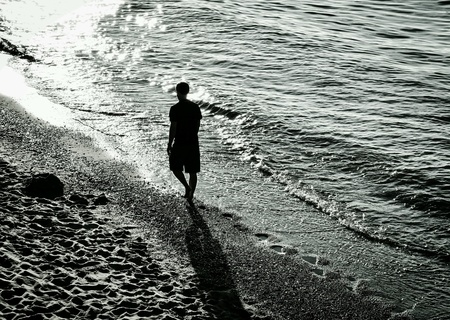man: Sillouette of a man walking a beach in black and white