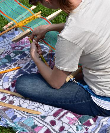Frau, die einen Handwebstuhl verwendet Standard-Bild - 83607474