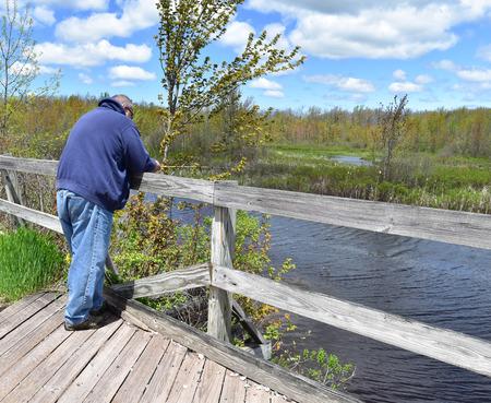 Mens die van een brug vist Stockfoto
