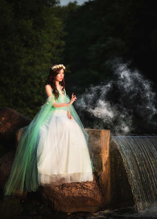 Young attractive girl dressed as fairy in evening garden portrait