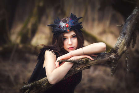 Cute young girl in dark dress fairy elf creature in the woods portrait